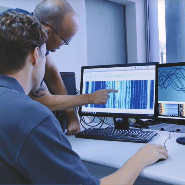 Engineer looking at DAS data on computer screens